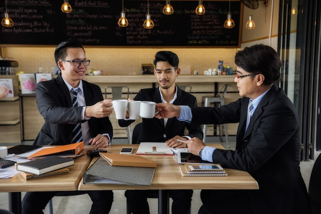 Businessman team clink hot coffee in cafe Premium Photo