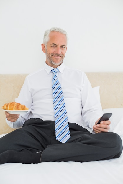 Businessman text messaging while holding croissant in bed Premium Photo