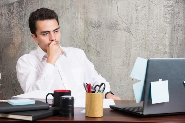 Uomo d'affari che pensa alla società alla scrivania dell'ufficio. Foto Gratuite