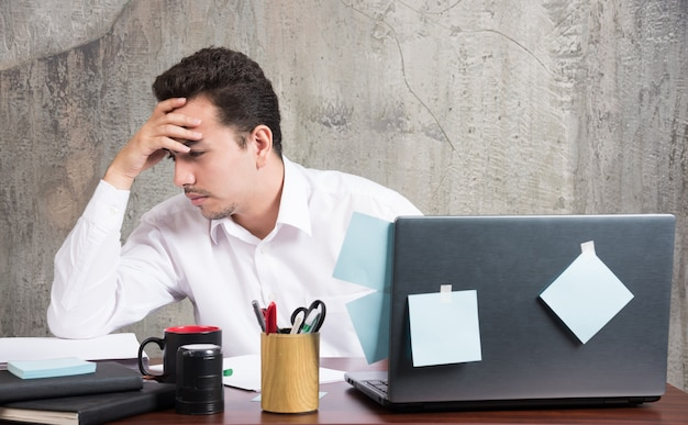 Imprenditore pensando a qualcosa alla scrivania in ufficio. Foto Gratuite