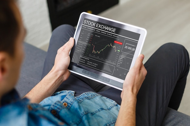 Businessman trading stocks with tablet and graph Premium Photo