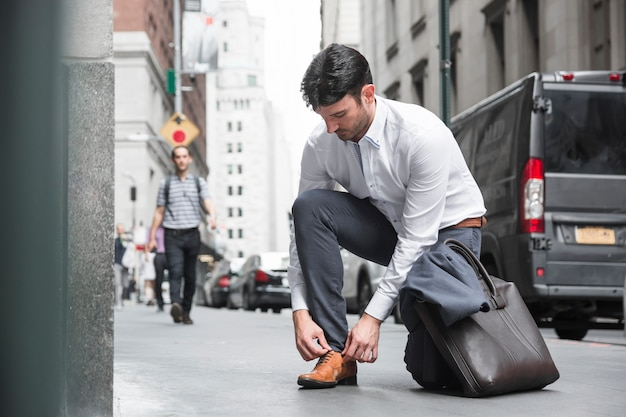 Businessman tying laces near road Free Photo