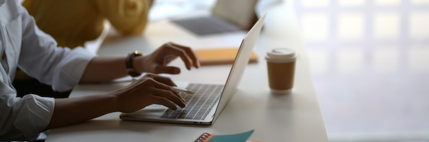 Businessman typing on laptop  in co-working space Premium Photo