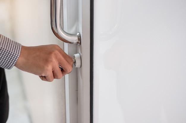 Businessman  unlocking doorknob to open the door in the office Premium Photo
