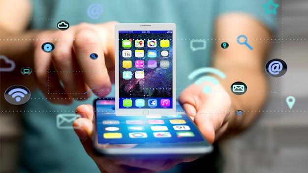 앱과 소셜 아이콘으로 태블릿을 둘러싼 스마트 폰을 사용하는 사업가 프리미엄 사진