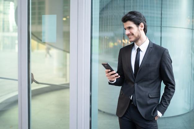 비즈니스 환경에서 자신의 스마트 폰에서 앱을 사용하는 사업가 프리미엄 사진