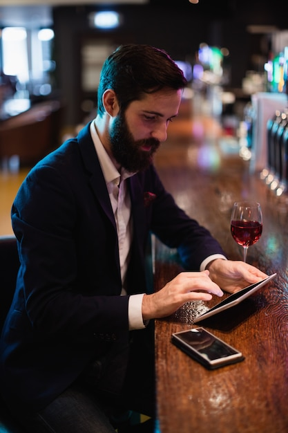 Businessman using digital tablet with wine glass and mobile phone on counter Free Photo