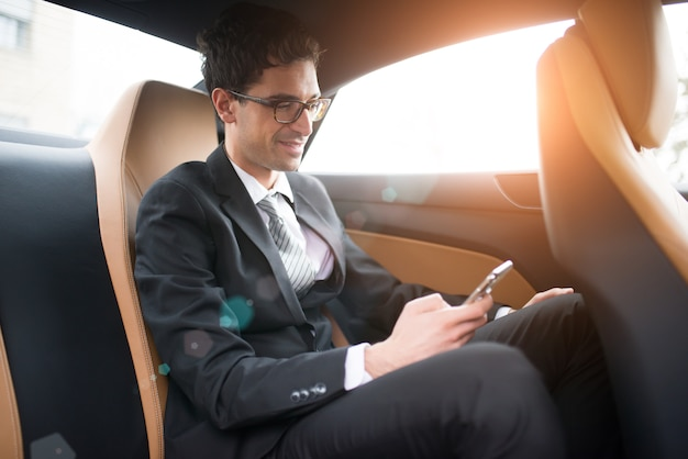 Businessman using his mobile phone in the back seat of a car Premium Photo