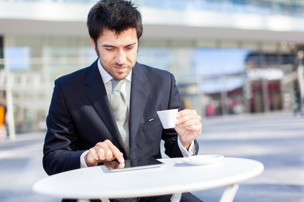 Businessman using his tablet in a coffee shop Premium Photo