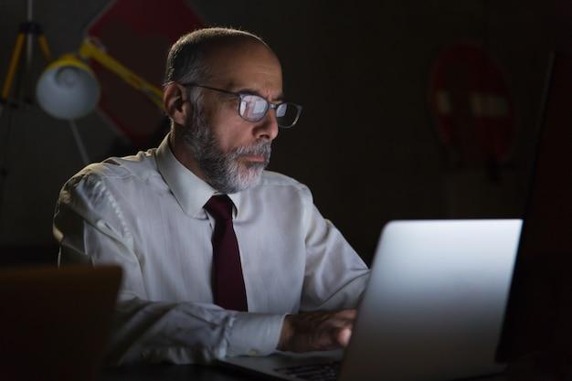 Businessman using laptop in dark office Free Photo