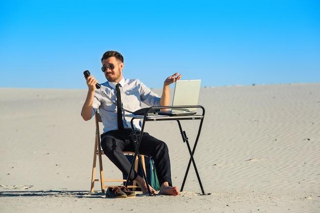 Businessman using laptop in a desert Free Photo