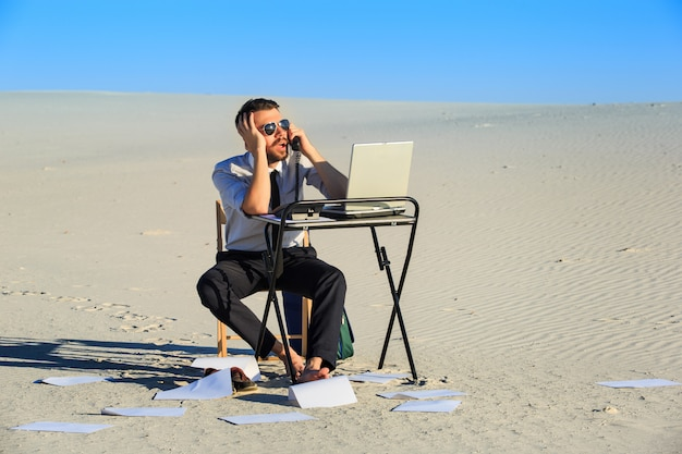 Businessman using laptop in a desert Free Photo