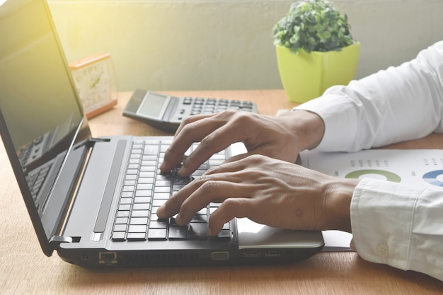 Businessman using laptop with analysis financial graph and chart. Premium Photo