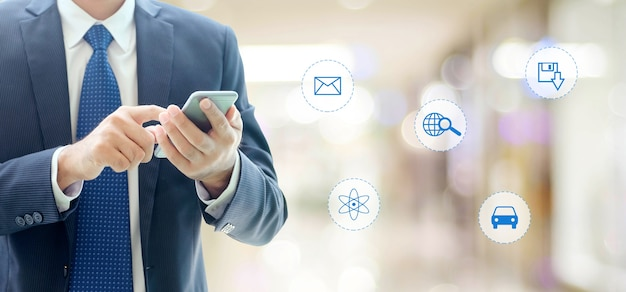 Businessman using smart phone with internet of things icon on blurred background, business and technology concept Premium Photo