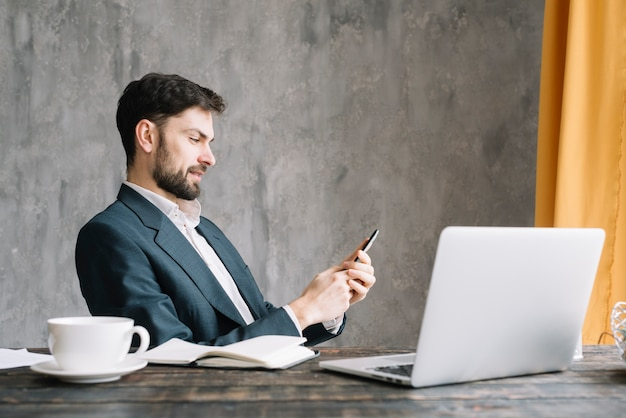 Businessman using smartphone near laptop Free Photo