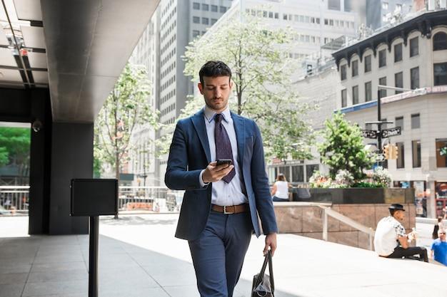 Businessman using smartphone on street Free Photo