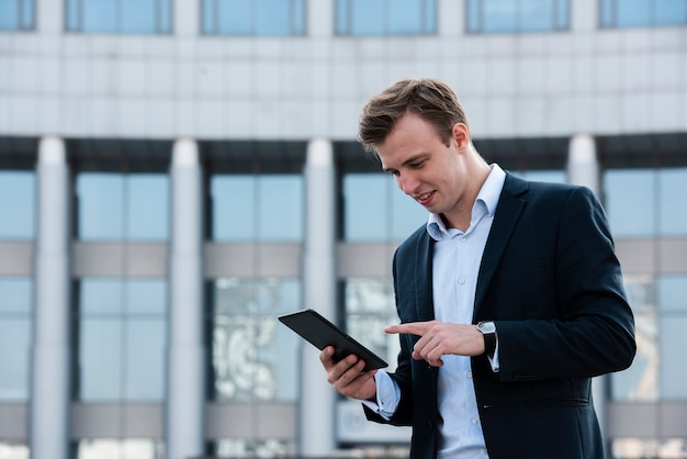 Businessman using tablet near building Free Photo