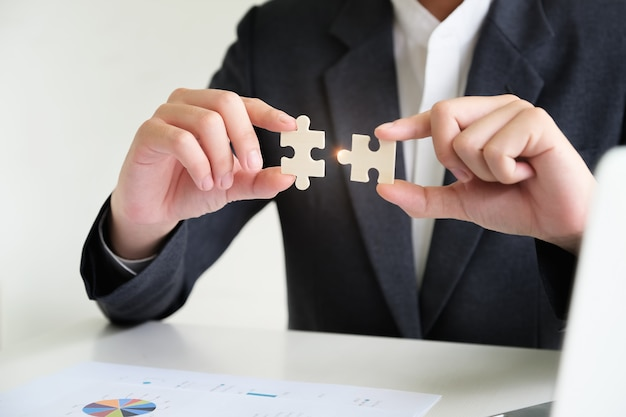 Businessman using two hands trying to connect couple puzzle piece, jigsaw alone wooden puzzle against. Premium Photo