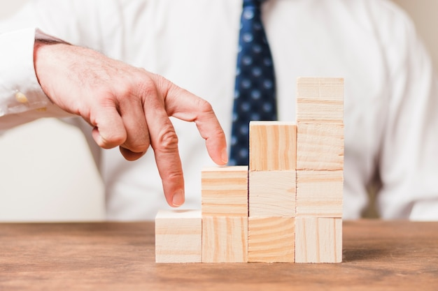 Businessman using wooden pieces Free Photo