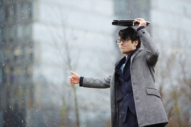 Businessman waiting for taxi in snow Free Photo