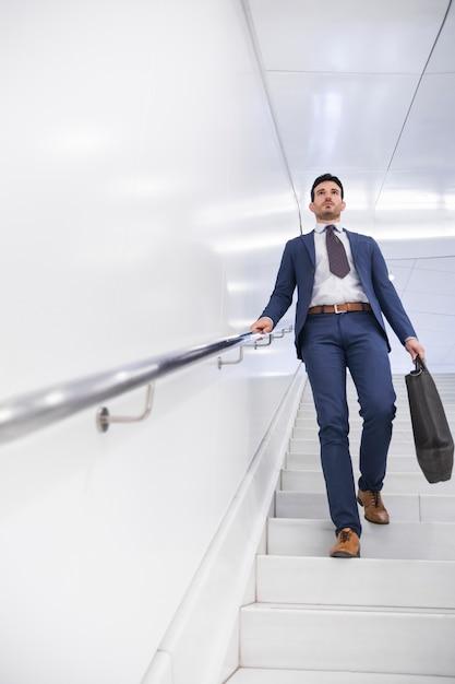 Businessman walking down steps Free Photo