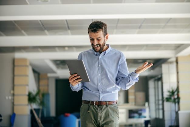 그의 회사의 홀에서 걷고 태블릿을 들고 사업가. 프리미엄 사진