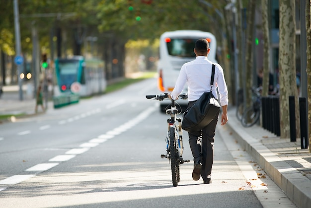 Businessman walking with bike in street after work Free Photo
