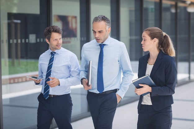 Businessman walking with colleagues outside office building Free Photo