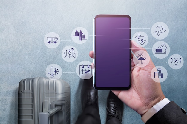 Businessman walking with suitcase and using tablet for travel management Premium Photo