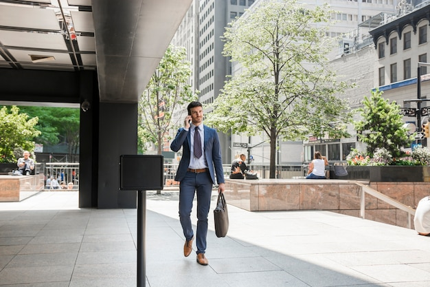 Businessman walking to work and speaking on phone Free Photo