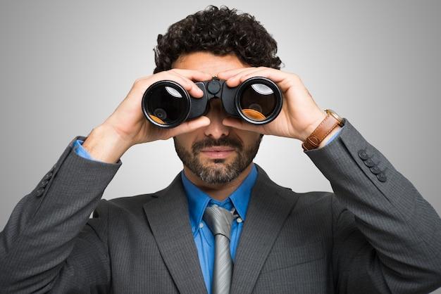 Businessman watching through binoculars Premium Photo