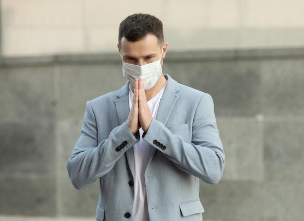 Бизнесмен в маске для лица и приветствие намасте, чтобы предотвратить распространение вируса Premium Фотографии