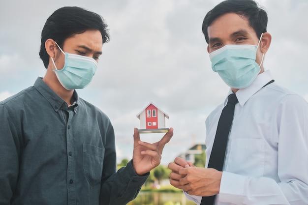 Бизнесмен в маске для лица, продавец продают домой клиенту Premium Фотографии