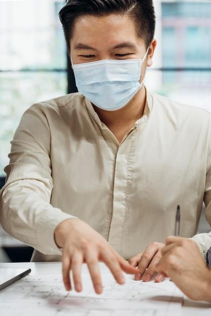 Uomo d'affari che indossa maschere mediche al lavoro Foto Gratuite