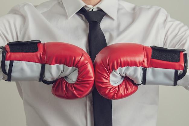 一緒に彼の拳をぶつけて赤いボクシングを着ているビジネスマン Premium写真
