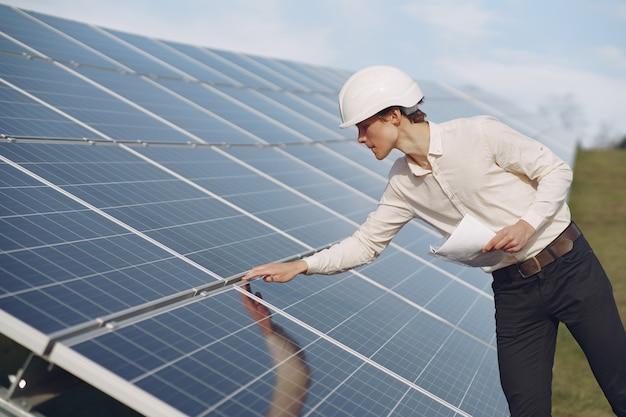 Businessman in a white helmet near solar battery Free Photo