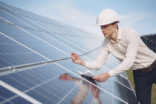 Businessman in a white helmet near solar battery Free Photo