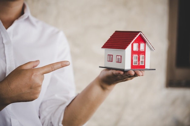 Businessman in white shirt holding a small house in hand Premium Photo