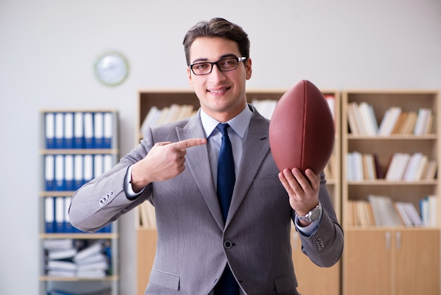 Businessman with american football in office Premium Photo