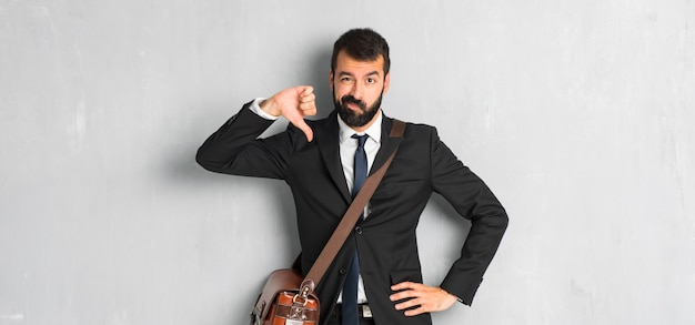 Businessman with beard showing thumb down sign with negative expression Premium Photo