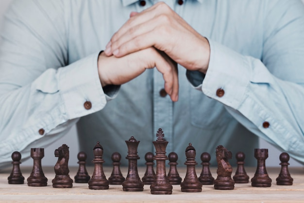 Businessman with clasped hands a brainstorming planning strategy in competition success play , concept strategy and successful management or leadership Premium Photo