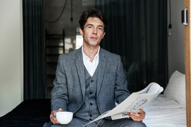 Businessman with coffee cup reading newspaper Free Photo