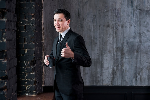 Businessman with coffee cup showing thumb up and looking at camera Free Photo