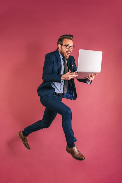 Businessman with computer jumping Premium Photo