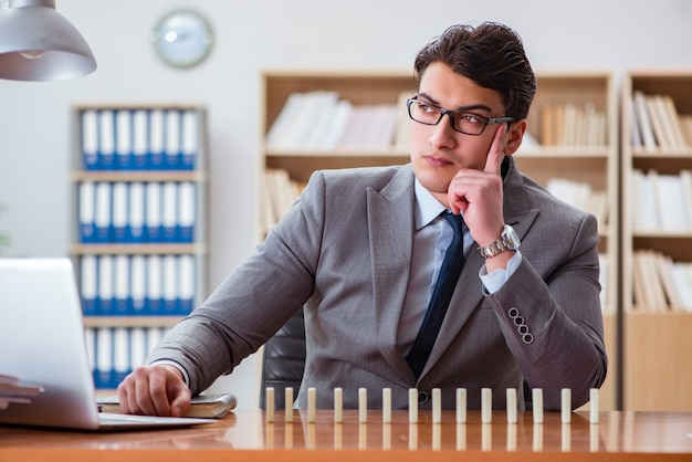Businessman with dominoes in the office Premium Photo
