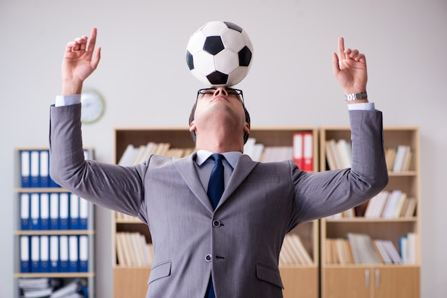 Businessman with football ball in office Premium Photo