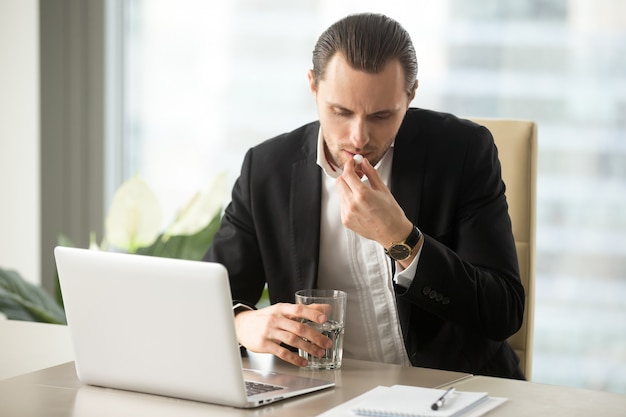 Businessman with glass of water takes round pill Free Photo