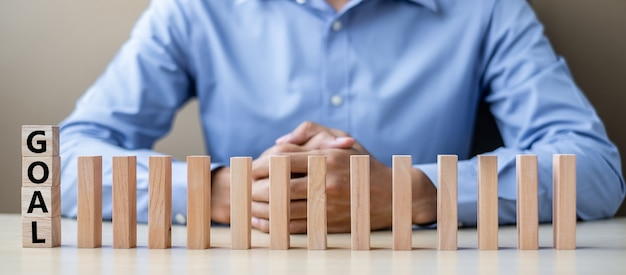 Businessman with goal wooden blocks or dominoes. business Premium Photo