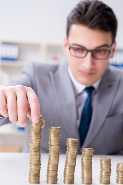 Businessman with golden coins in business growth concept Premium Photo