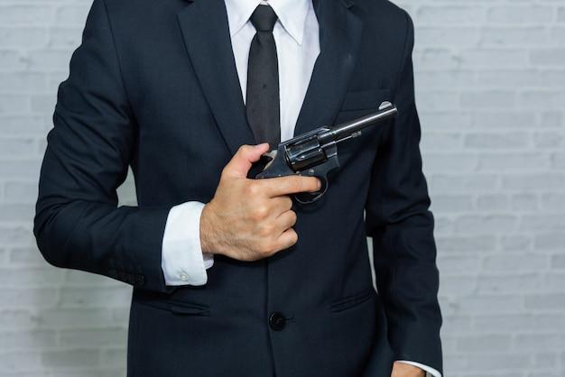 Businessman with gun on gray background Premium Photo